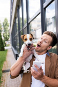 excited man with mobile phone holding jack russell terrier dog on city street