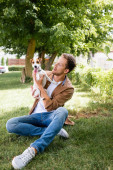 man in brown shirt and jeans holding jack russell terrier dog while sitting on lawn in park
