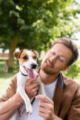 young man holding white jack russell terrier dog with brown spots on head in park