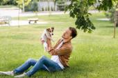 Fotografie Junger Mann in braunem Hemd und Jeans hält Jack Russell Terrier Hund auf dem Rasen