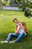 mladý muž v hnědé košili a džíny sedí na trávě a mazlení jack Russell teriér pes