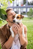 mladý muž se zavřenýma očima drží bílý jack Russell teriér pes s hnědými skvrnami na hlavě