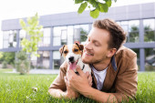 young man cuddling jack russell terrier dog while lying on green lawn
