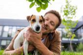 selektivní zaměření mladého muže mazlení jack Russell teriér pes zatímco ležící na zelené trávě