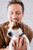 Selective focus of man hugging jack russell terrier looking at camera near building