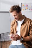 Obchodník v ležérní oblečení pomocí smartphone při práci v kanceláři