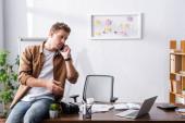 Mladý podnikatel mluví na smartphone v blízkosti notebooku a vr sluchátka na stole v kanceláři