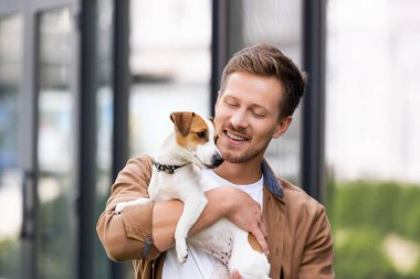 young man holding white jack russell terrier dog with brown sports on head
