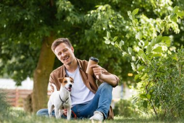 Young man in brown shirt and jeans holding disposable cup while sitting on grass near jack russell terrier dog stock vector