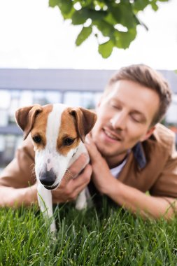 selective focus of young man lying on green grass with jack russell terrier dog