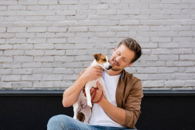 Young man embracing jack russell terrier near building on urban street stock vector