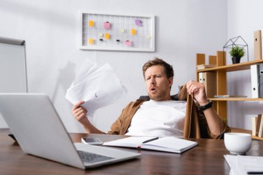 Selective focus of businessman holding documents while suffering from heat in office stock vector