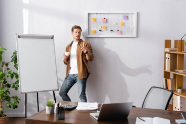 Selective focus of businessman with cup of coffee having idea near whiteboard and laptop in office stock vector