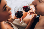Selective focus of young couple looking at each other while toasting with wine on bed