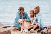 Fotografie Selektiver Fokus der Familie mit Tochter, die Golden Retriever am Meer streichelt