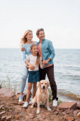 Selective focus of man embracing wife and daughter near golden retriever on seaside