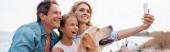 Horizontal image of family with golden retriever taking selfie on beach