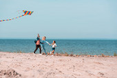 Selective focus of family with kite running on beach sand near sea
