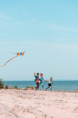 Selective focus of man holding kite while running near family on beach
