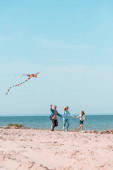 Selective focus of family holding hands while running with kite on beach near sea