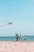 Selective focus of family running with kite on seaside