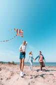 Selective focus of girl holding kite near parents on beach