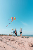Selective focus of kid running with kite near parents on beach