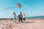 Selective focus of kid holding kite while running on beach near parents
