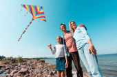 Low angle view of man hugging daughter with kite and wife during vacation on seaside