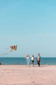 Selective focus of woman holding kite while running with family on beach