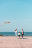 Selective focus of woman with kite walking near daughter and husband on beach