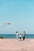 Selektivní zaměření ženy s drakem chůze v blízkosti dcery a manžela na pláži