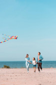 Selective focus of family running with kite on beach during weekend