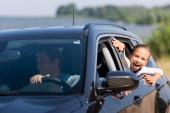 Selektiver Fokus des aufgeregten Mädchens, das durch das Autofenster in die Nähe des Vaters blickt
