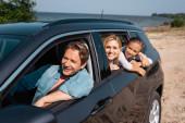Selektiver Fokus der Familie, die tagsüber im Auto am Meer unterwegs ist