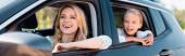 Panoráma felvétel izgatott nő néz félre, miközben utazik a lánya az autóban