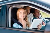 Szelektív fókusz töprengő nő digitális tabletta néz el a közeli család auto