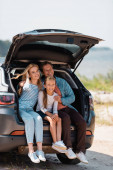 Family with daughter sitting in car trunk during vacation