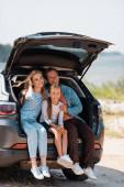 Familie mit Tochter sitzt im Urlaub im Kofferraum