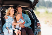 Man embracing wife and daughter in truck of auto