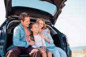 Mann umarmt Frau und Kind, während er draußen im Kofferraum des Autos sitzt