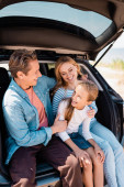 Photo Selective focus of kid sitting near mother and father in car trunk outdoors