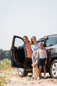 Selective focus of family with golden retriever looking at camera while standing near car outdoors
