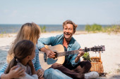 Selective focus of man playing acoustic guitar near wife and daughter on beach