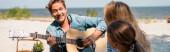 Horizontální obraz muže hrajícího na akustickou kytaru v blízkosti rodiny na pláži