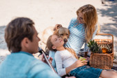 Selective focus of woman petting golden retriever near daughter and husband with acoustic guitar on beach