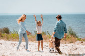 Selective focus of kid playing with parents in football near golden retriever on beach