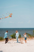 Family with golden retriever playing with football and kite on beach