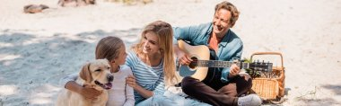 Panoramic shot of woman embracing child near golden retriever and husband with acoustic guitar on beach