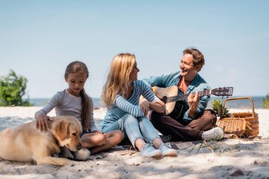 Selective focus of woman looking at husband playing acoustic guitar near daughter with golden retriever on beach